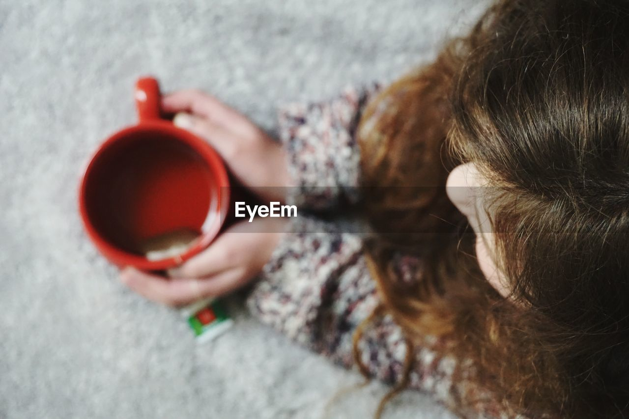 Directly Above Shot Of Girl Holding Tea On Bed