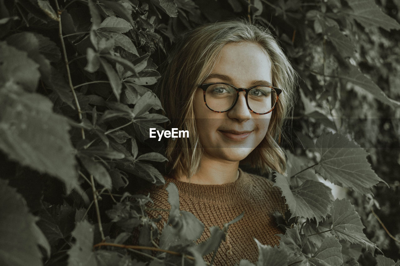 Close-up portrait of young woman in eyeglasses