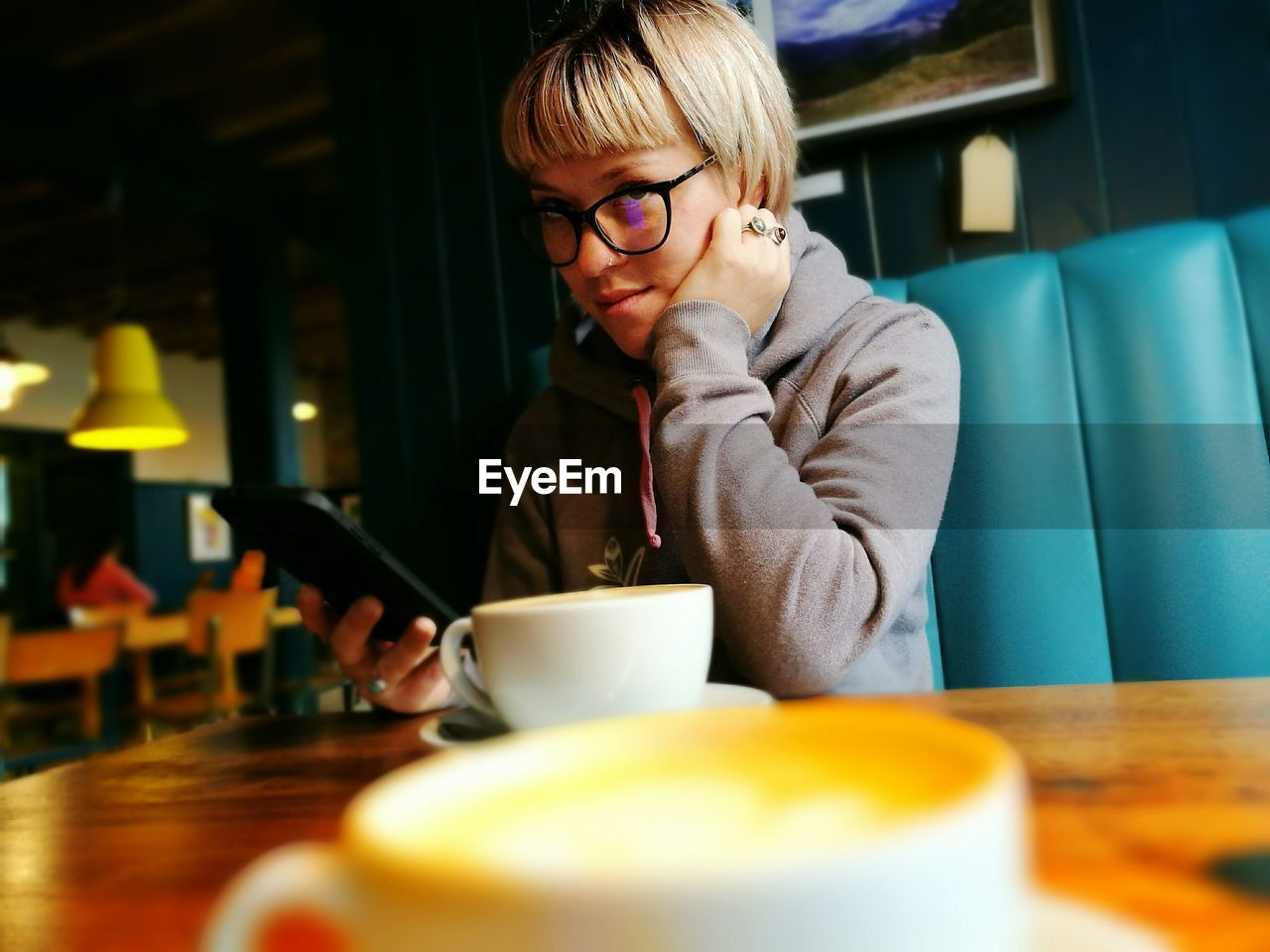 Woman Using Phone By Coffee Cup In Cafe