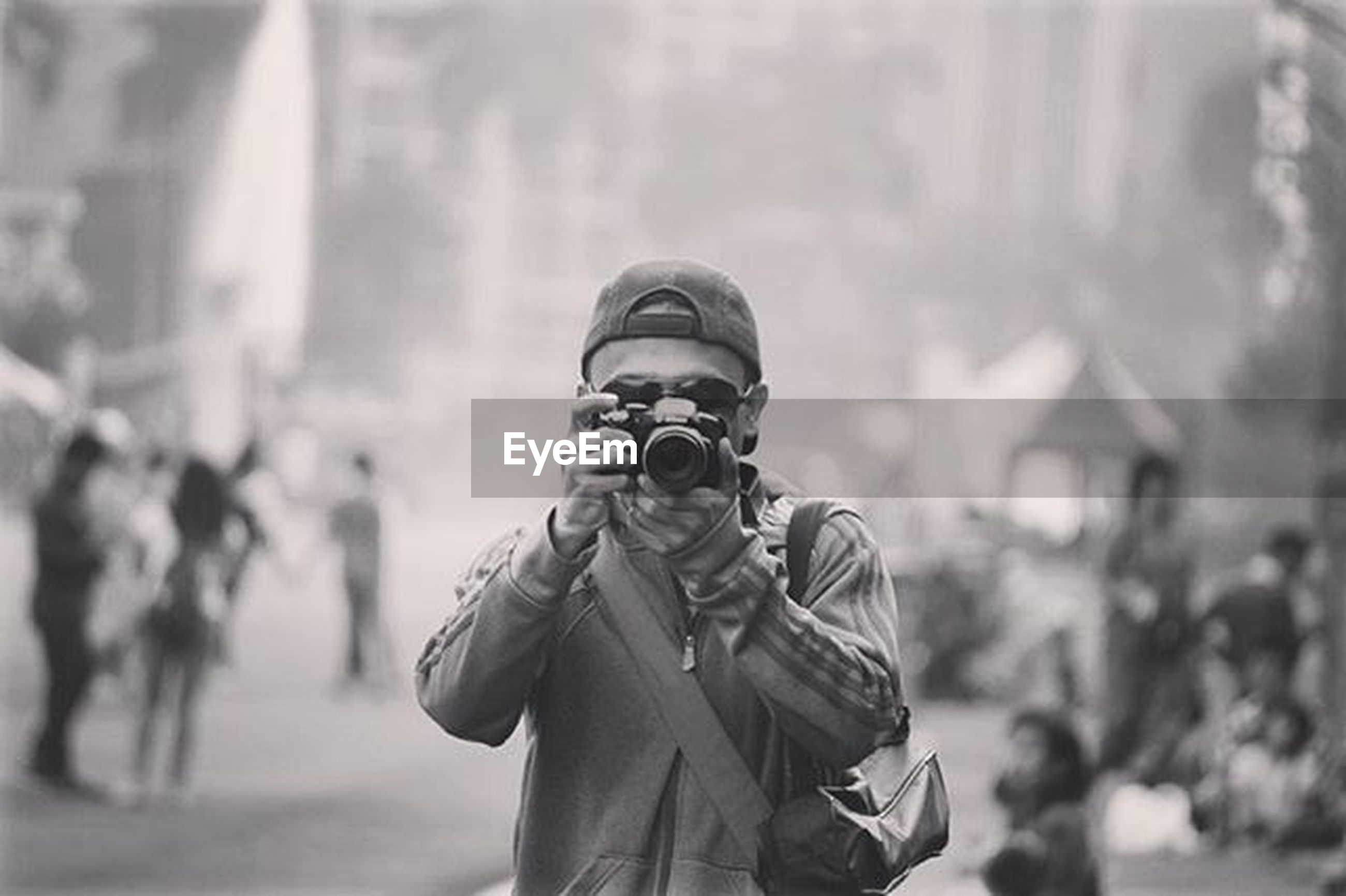 focus on foreground, lifestyles, men, leisure activity, standing, casual clothing, holding, rear view, warm clothing, waist up, human representation, day, young men, hat, outdoors, incidental people, headshot, three quarter length