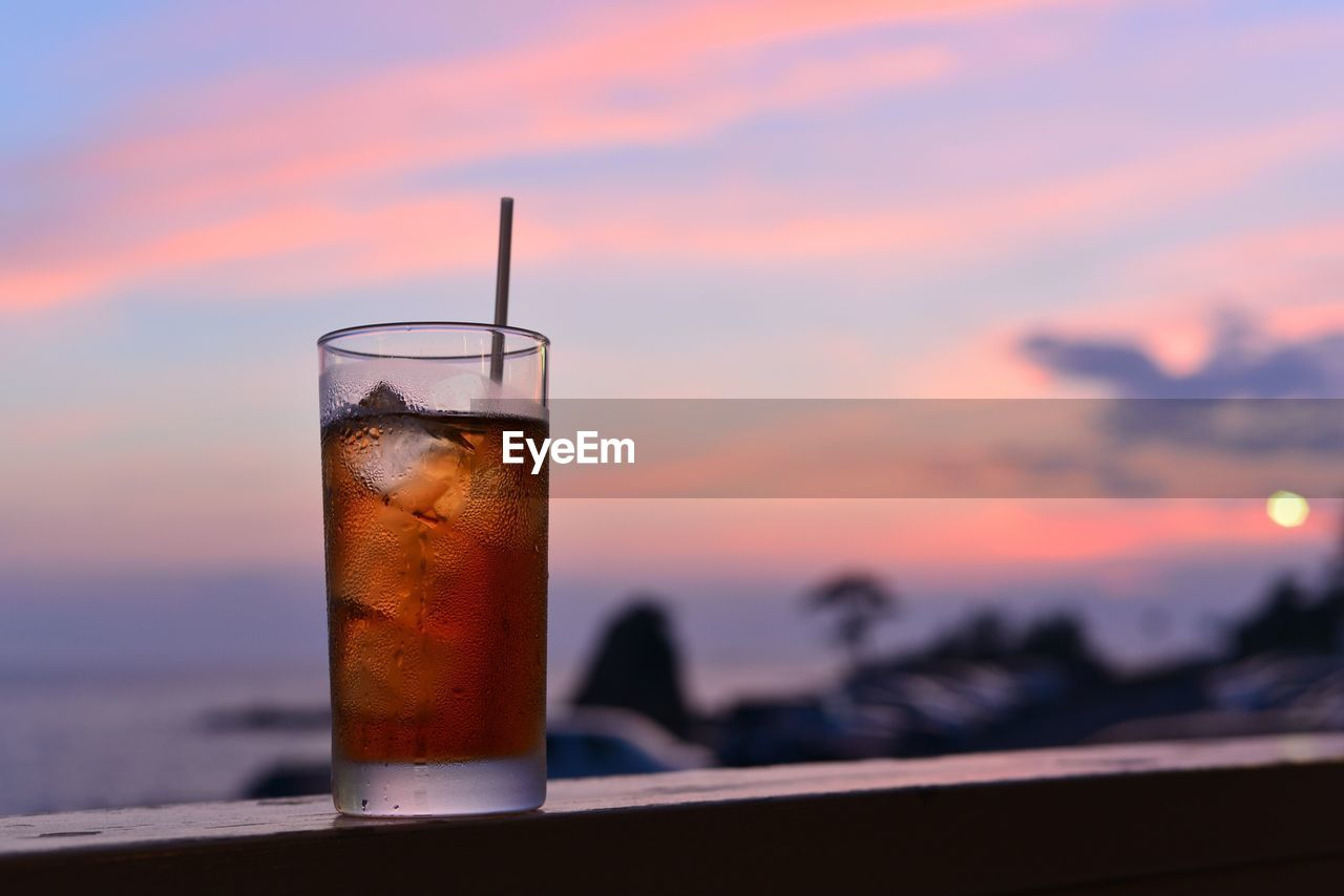 Close-Up Of Iced Tea On Retaining Wall Against Sky