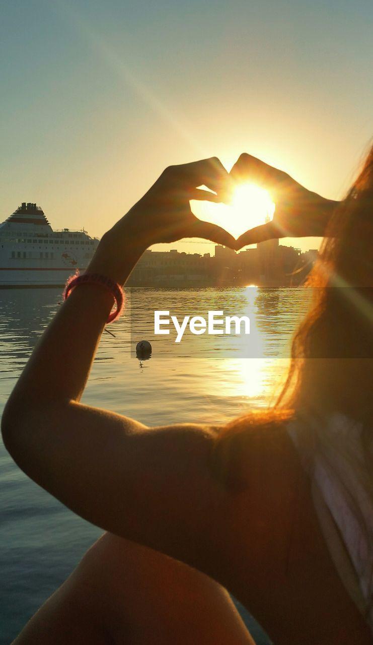 Rear view of woman making heart shape towards sun