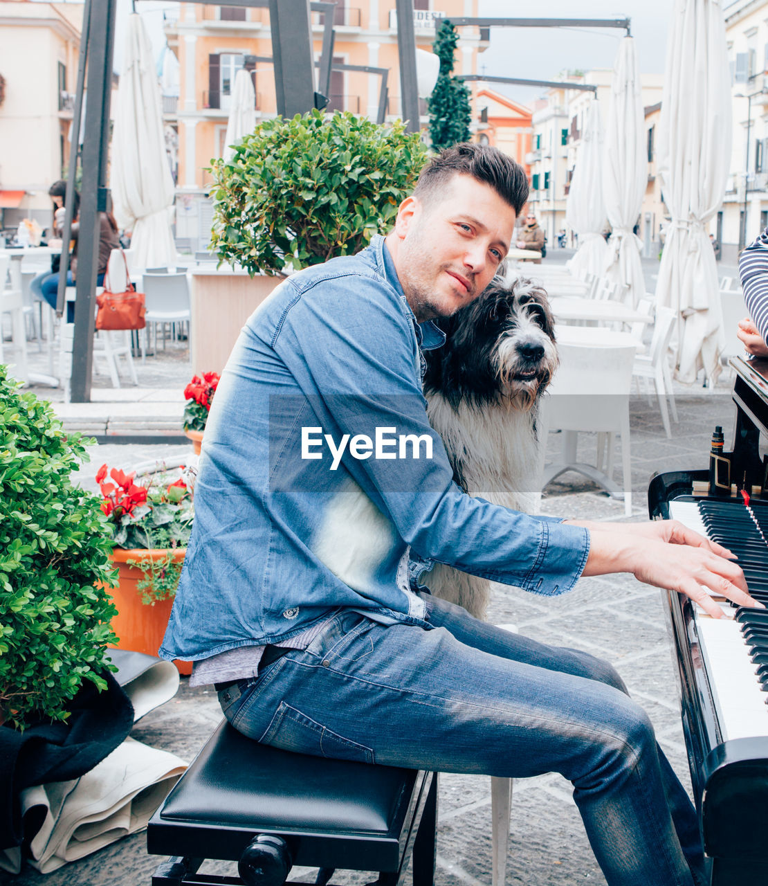 Portrait Of A Smiling Young Man Playing Piano With Dog