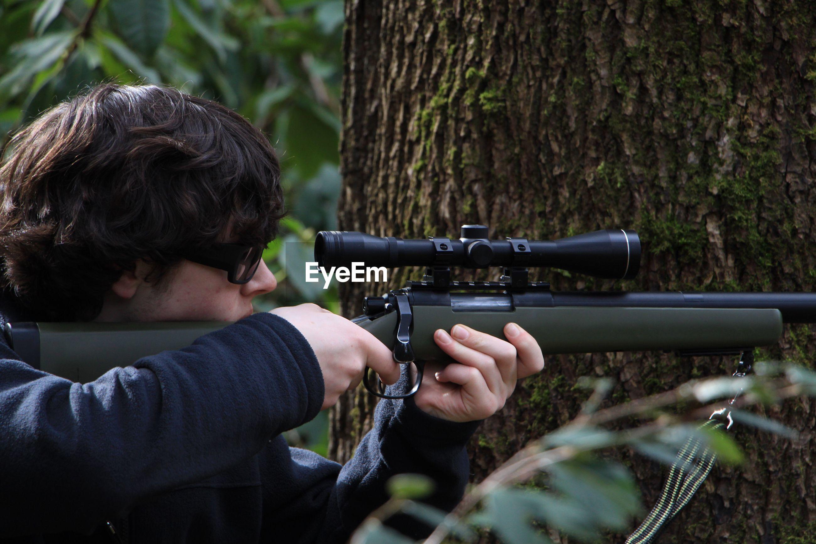 Man aiming gun by tree
