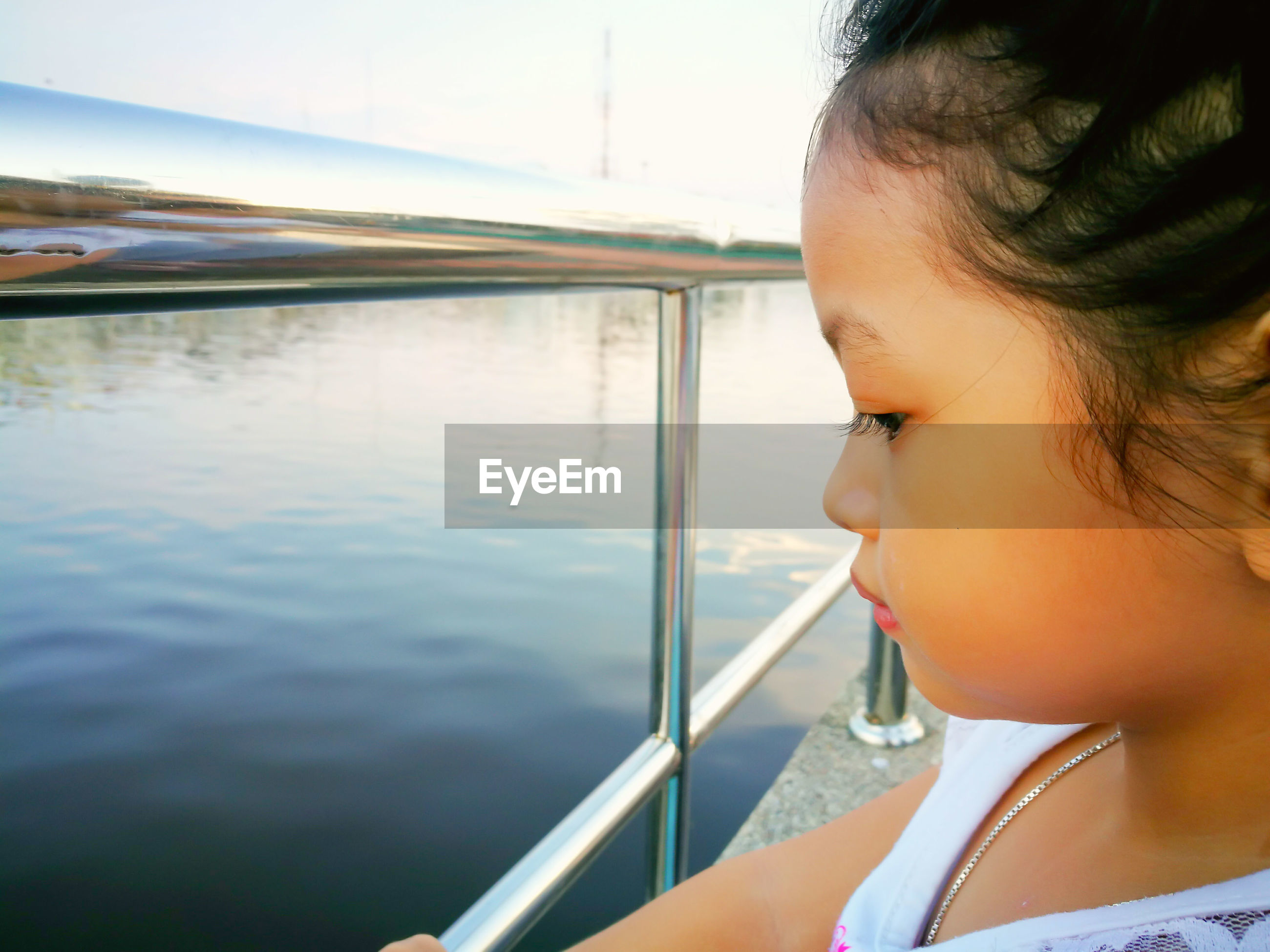 Close-up of girl standing by railing looking at lake