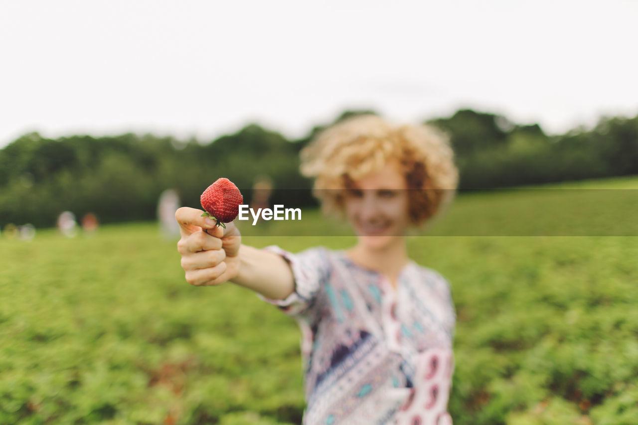 Woman showing a ripe strawberry