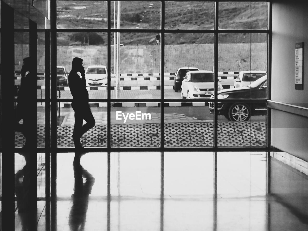 WOMAN WALKING ON GLASS WINDOW