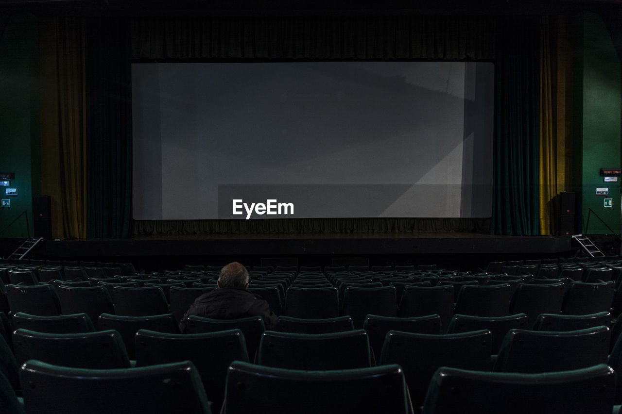 seat, chair, arts culture and entertainment, indoors, screen, movie theater, in a row, sitting, projection screen, rear view, people, adult, group of people, real people, stage theater, auditorium, empty, film industry, men, leisure activity, stage