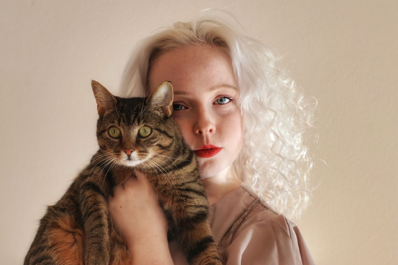 Portrait of woman with cat against gray background