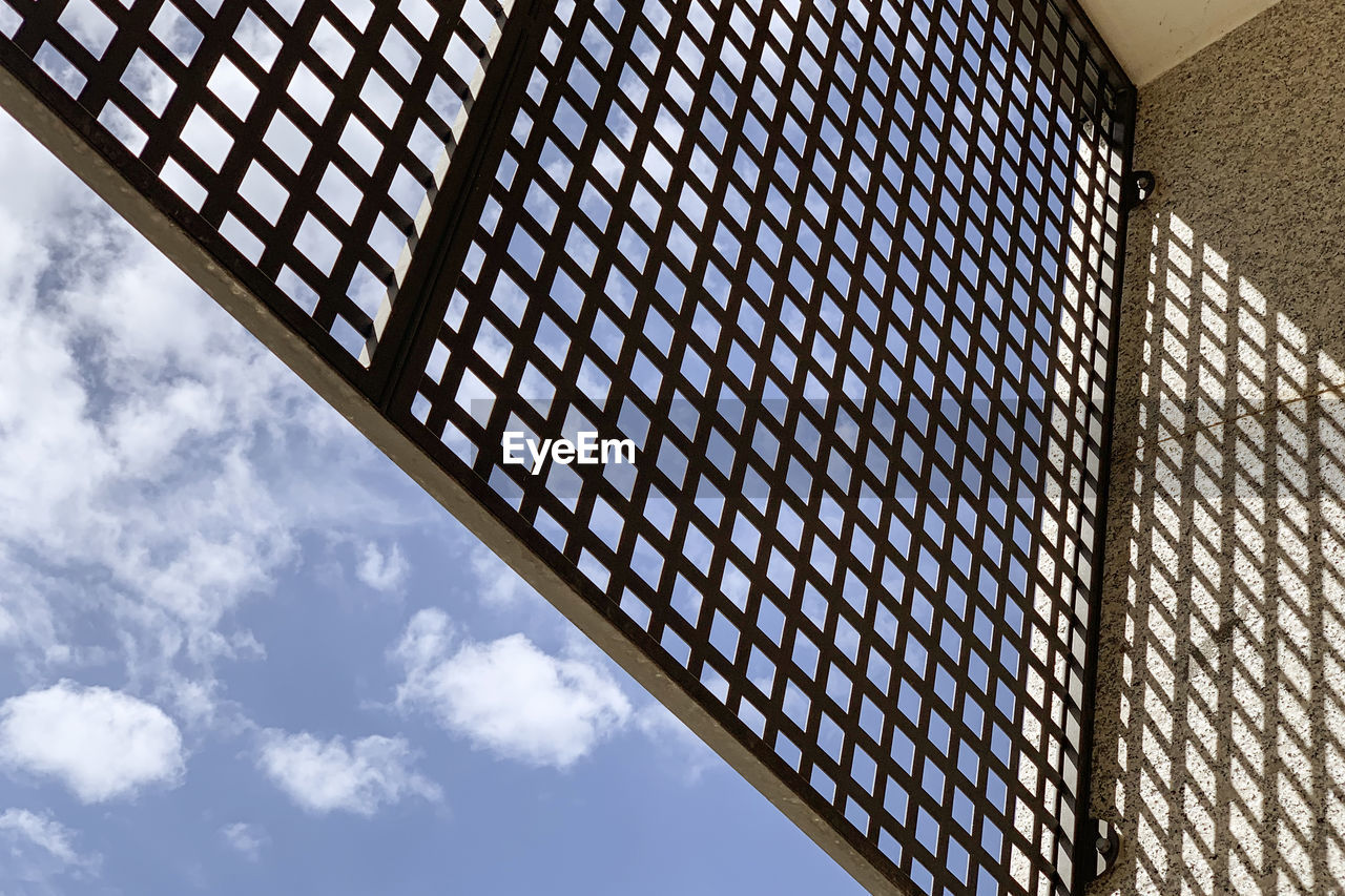 low angle view, built structure, architecture, sky, cloud - sky, pattern, day, no people, building, nature, sunlight, building exterior, glass - material, outdoors, design, modern, metal, blue, ceiling, skylight