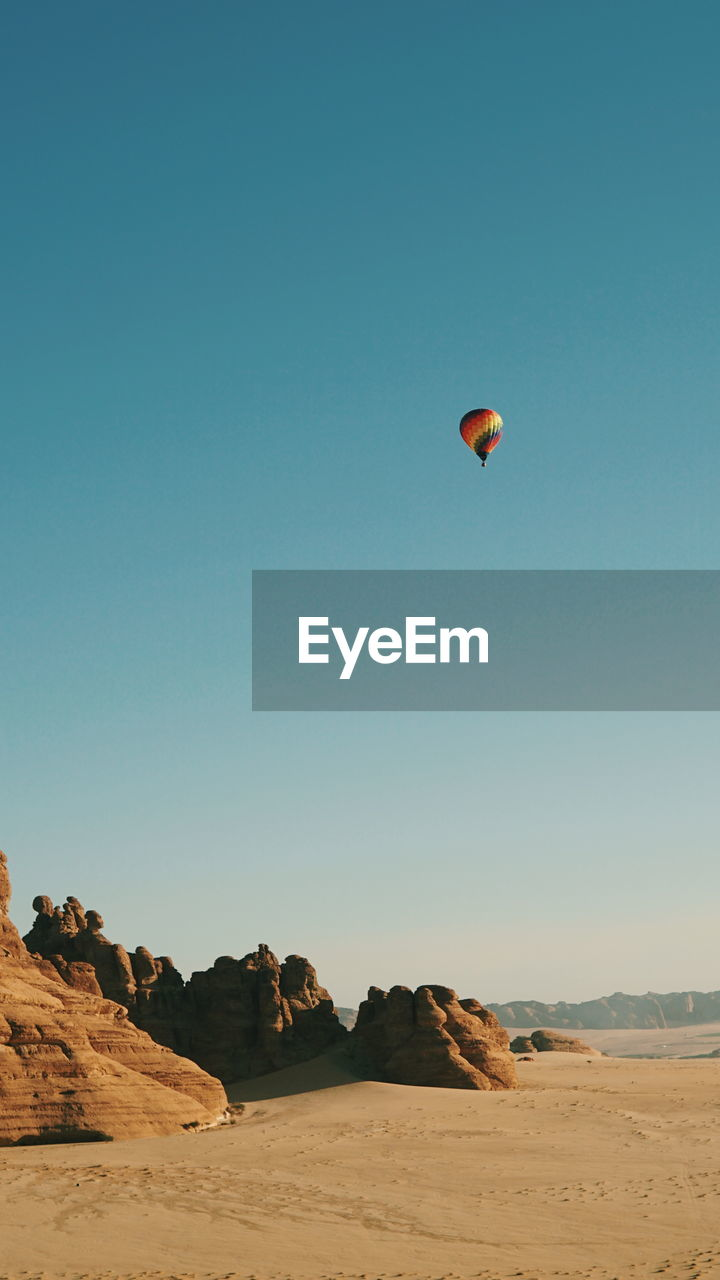 sky, adventure, land, copy space, extreme sports, parachute, clear sky, mid-air, beauty in nature, scenics - nature, nature, environment, flying, paragliding, desert, sport, landscape, day, tranquility, unrecognizable person, arid climate, climate