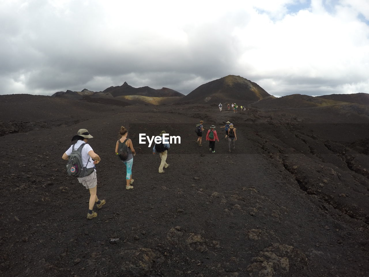 Rear View Of People Hiking On Mountain Against Cloudy Sky