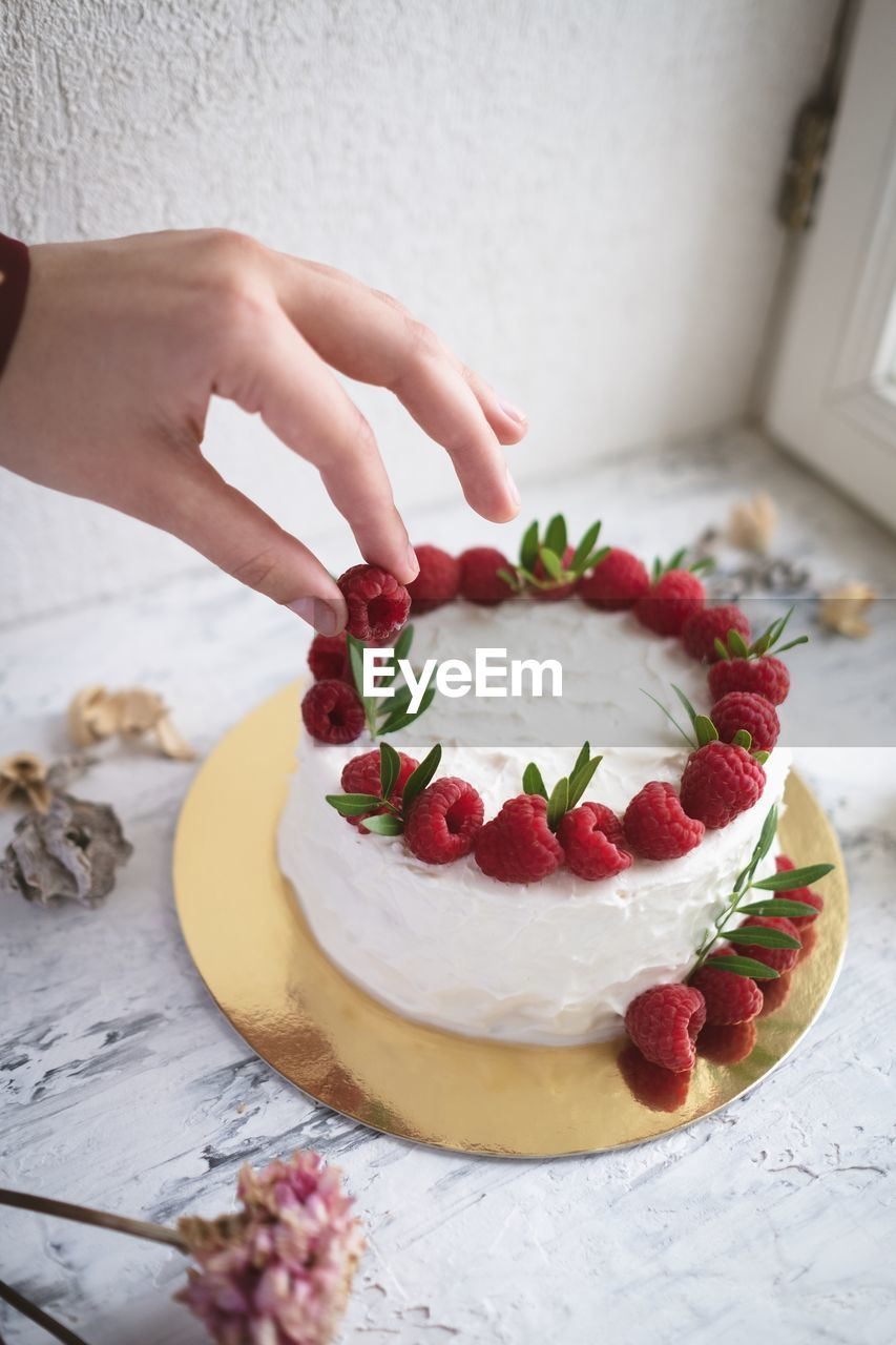 food and drink, food, human hand, hand, one person, human body part, fruit, sweet, freshness, berry fruit, indulgence, real people, dessert, sweet food, indoors, strawberry, healthy eating, temptation, high angle view, finger, preparing food