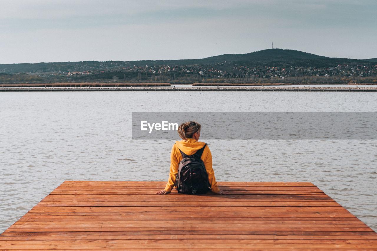 Full length of woman sitting on pier against sky
