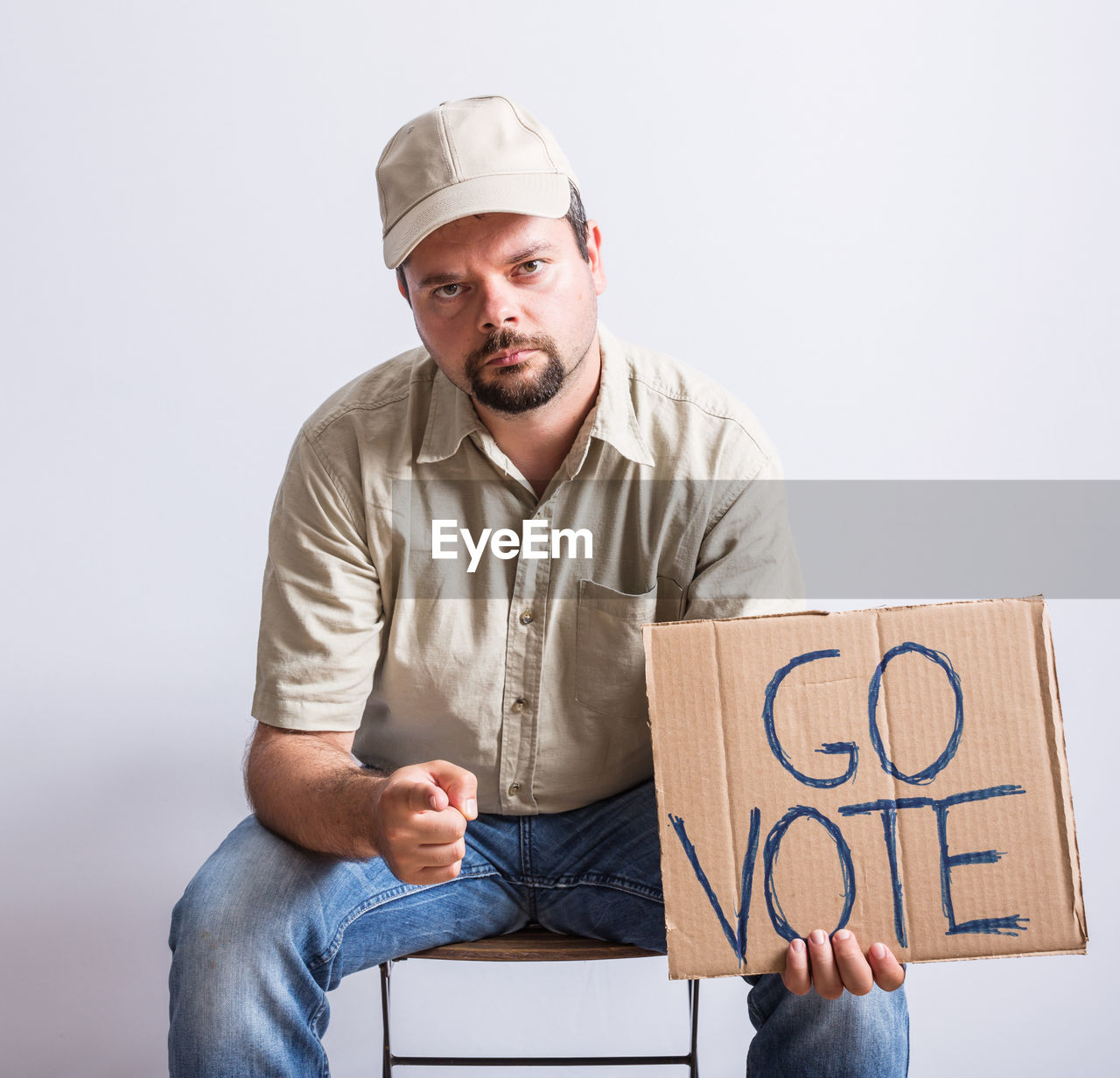 Portrait of delivery man holding cardboard with text while sitting against wall