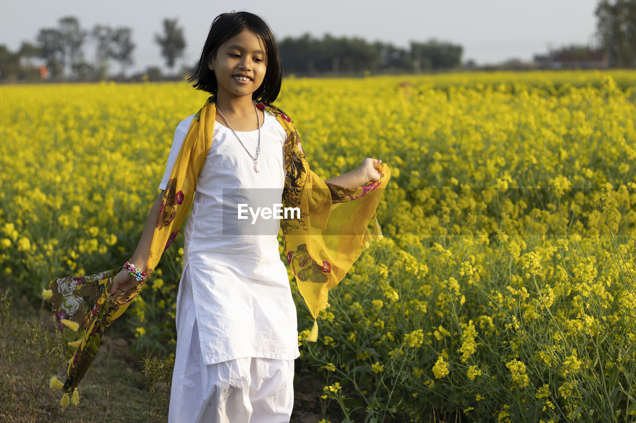 YOUNG WOMAN STANDING ON YELLOW FLOWER FIELD