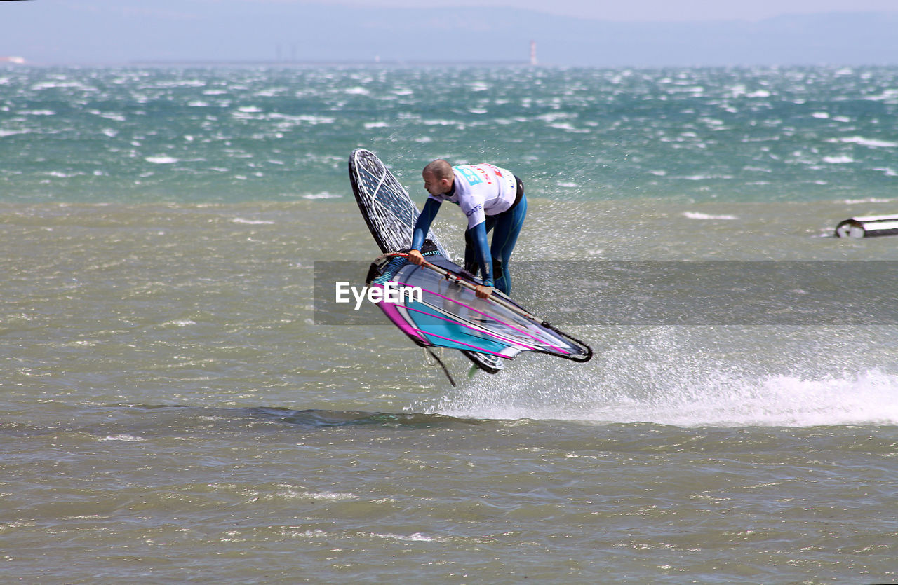 leisure activity, one person, sea, real people, water, sport, motion, surfing, nature, full length, lifestyles, outdoors, extreme sports, day, wave, adventure, standing, men, oar, sky, paddleboarding, people, adult