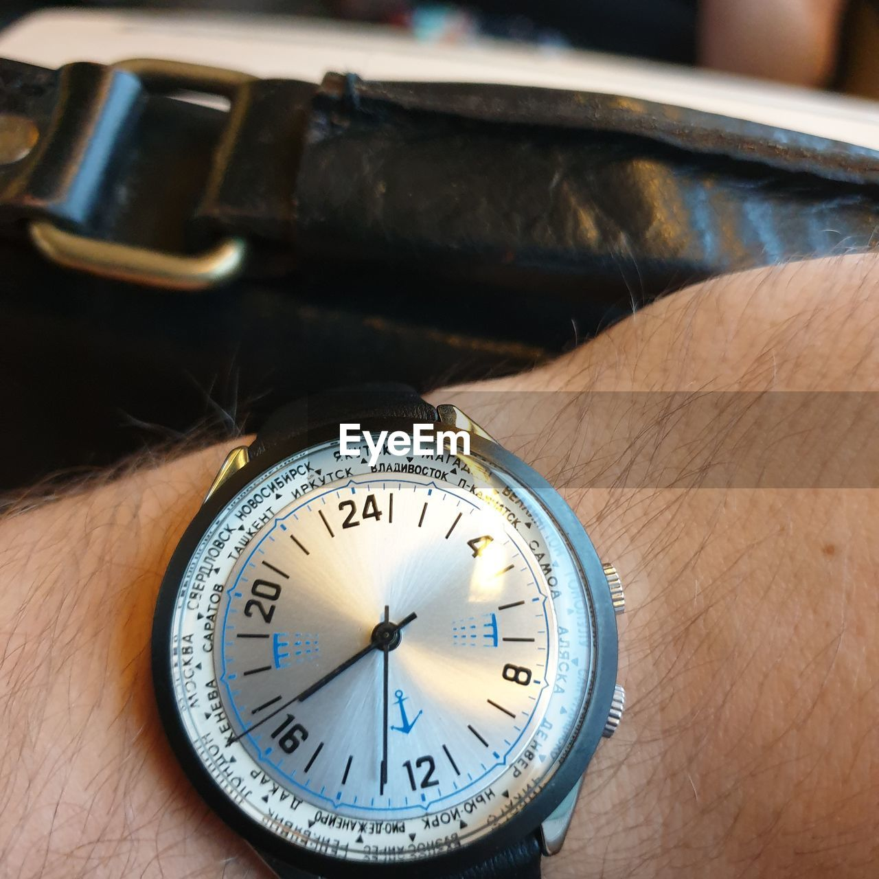 human hand, hand, human body part, watch, time, close-up, number, focus on foreground, real people, wristwatch, body part, one person, indoors, unrecognizable person, accuracy, table, personal accessory, human finger, finger, clock, human limb