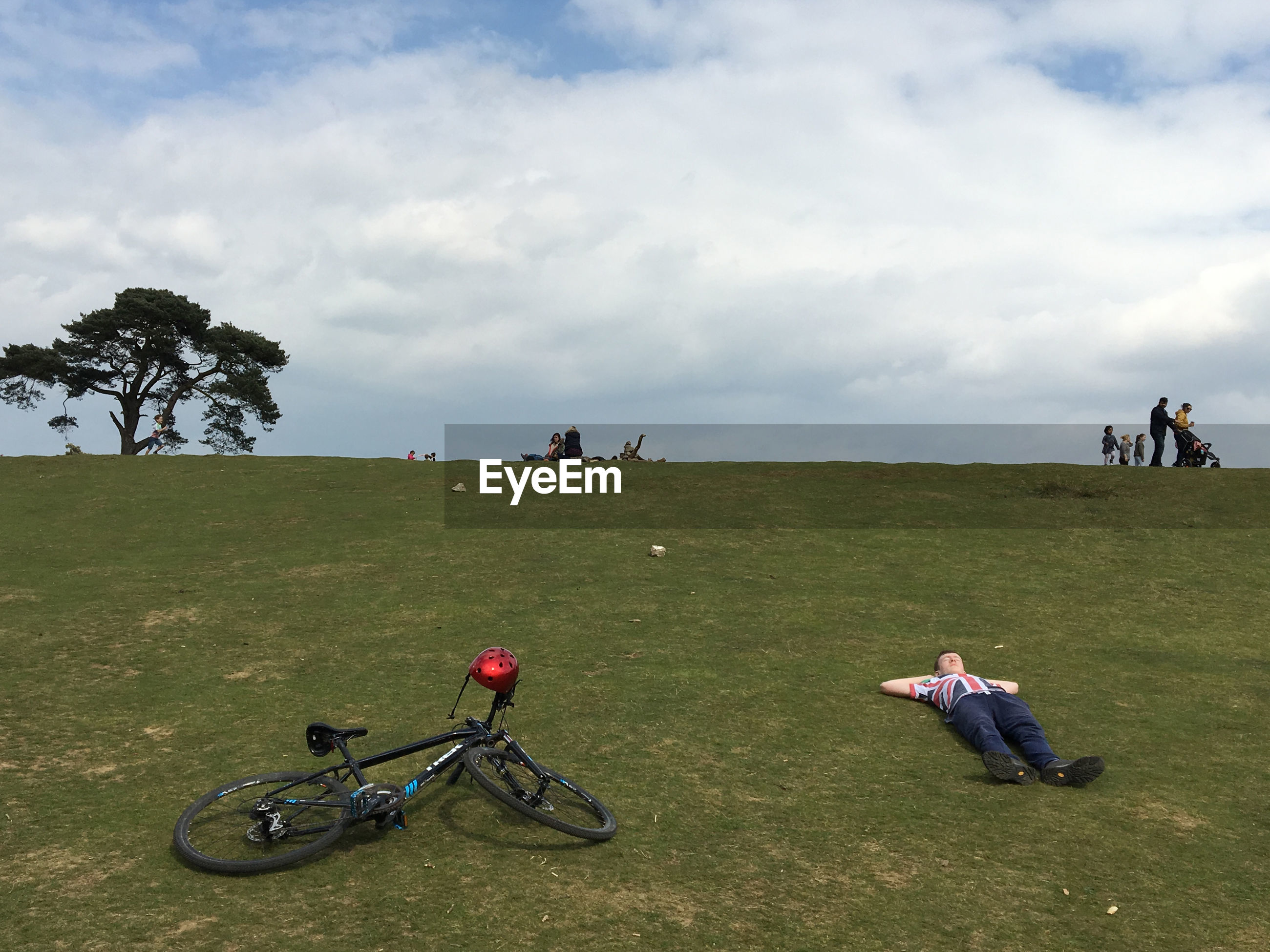 PEOPLE SITTING ON BICYCLE ON FIELD