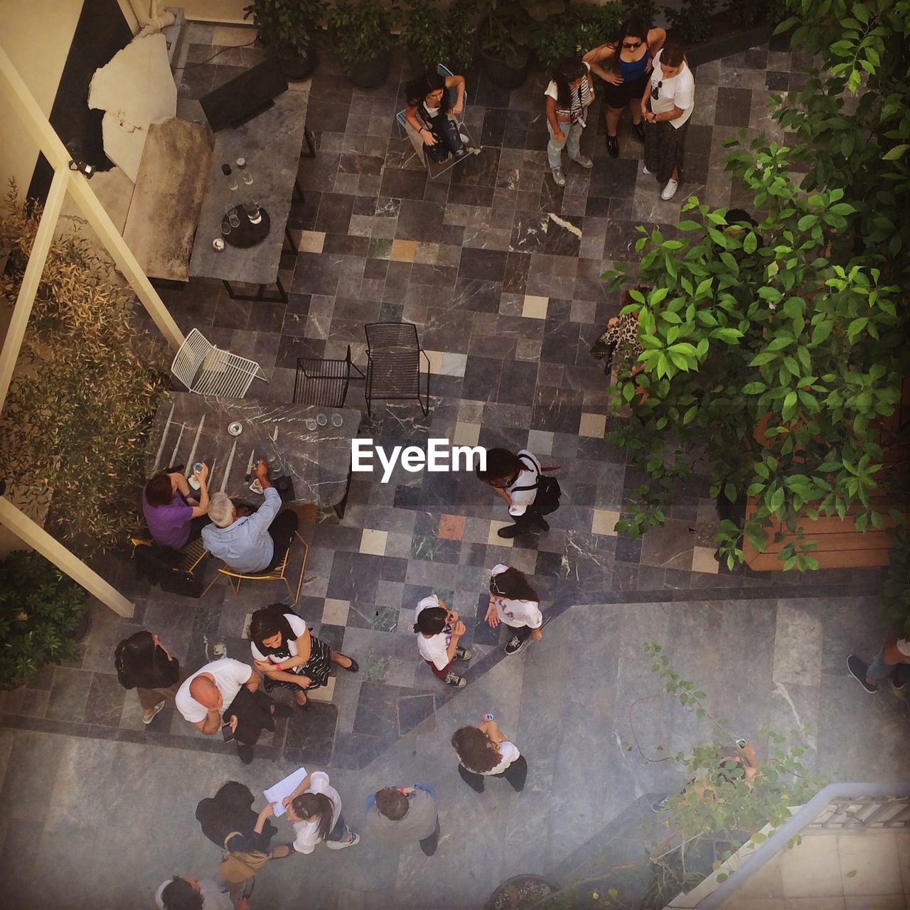 high angle view, women, men, large group of people, meeting, real people, talking, togetherness, business, table, discussion, sitting, chair, cafe, day, businessman, coworker, adult, young adult, young women, outdoors, people, social gathering, adults only