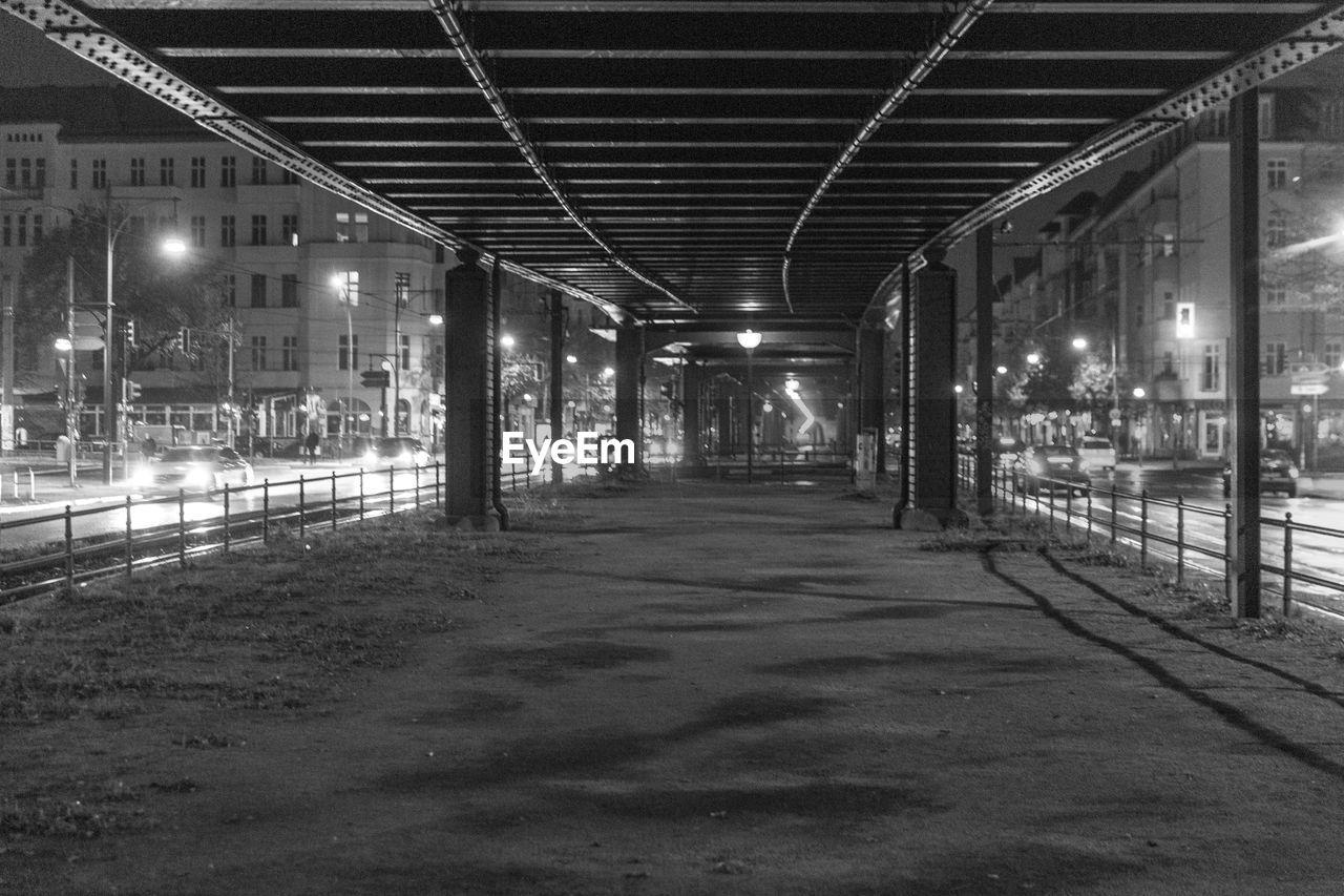 Empty road amidst illuminated buildings at night