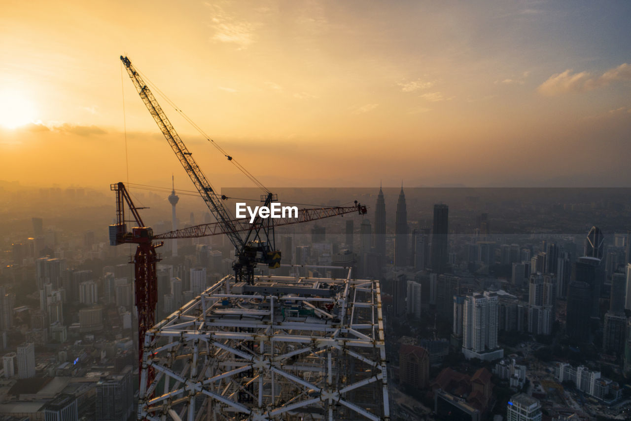 Cranes At Construction Site In City Against Sky During Sunset