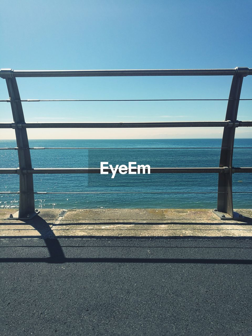 water, sea, railing, no people, scenics, clear sky, nature, day, sunlight, outdoors, road, blue, horizon over water, beauty in nature, sky