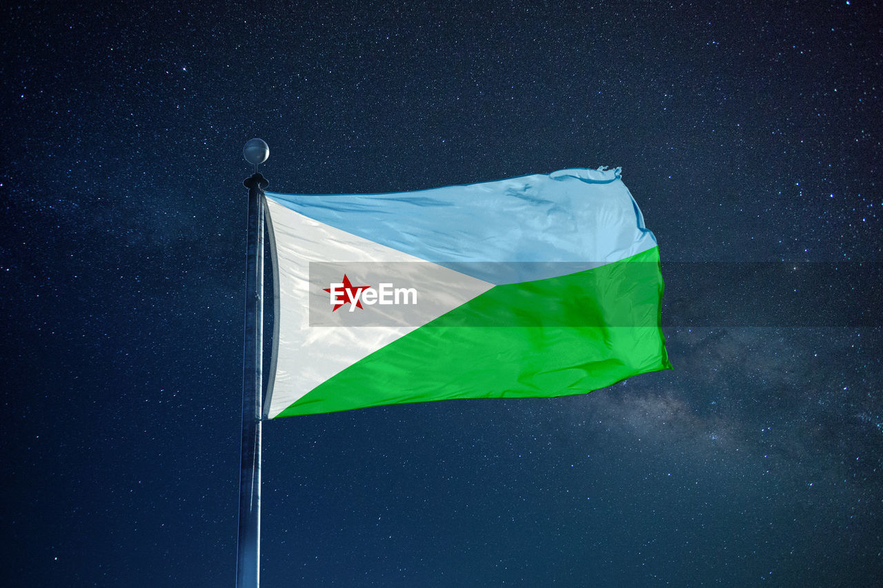 Low angle view of djibouti flag against star field sky