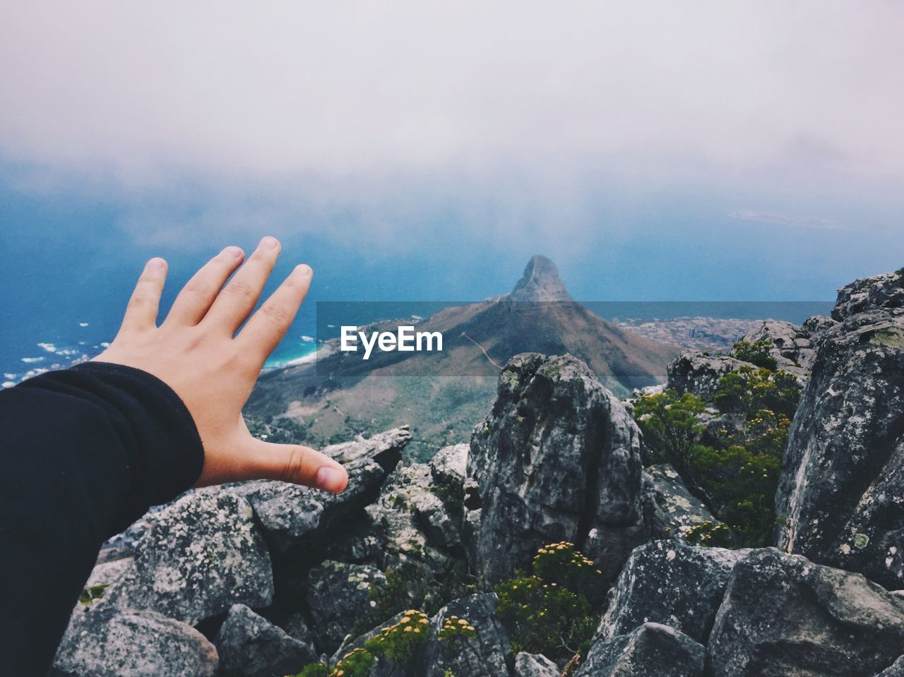 Person Reaching Towards Mountain Against Sky