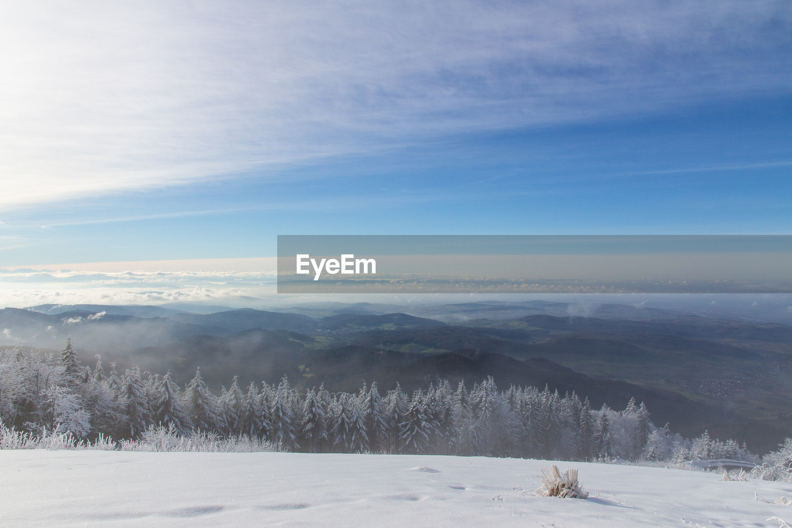 Scenic view of snowcapped landscape against mountains in winter