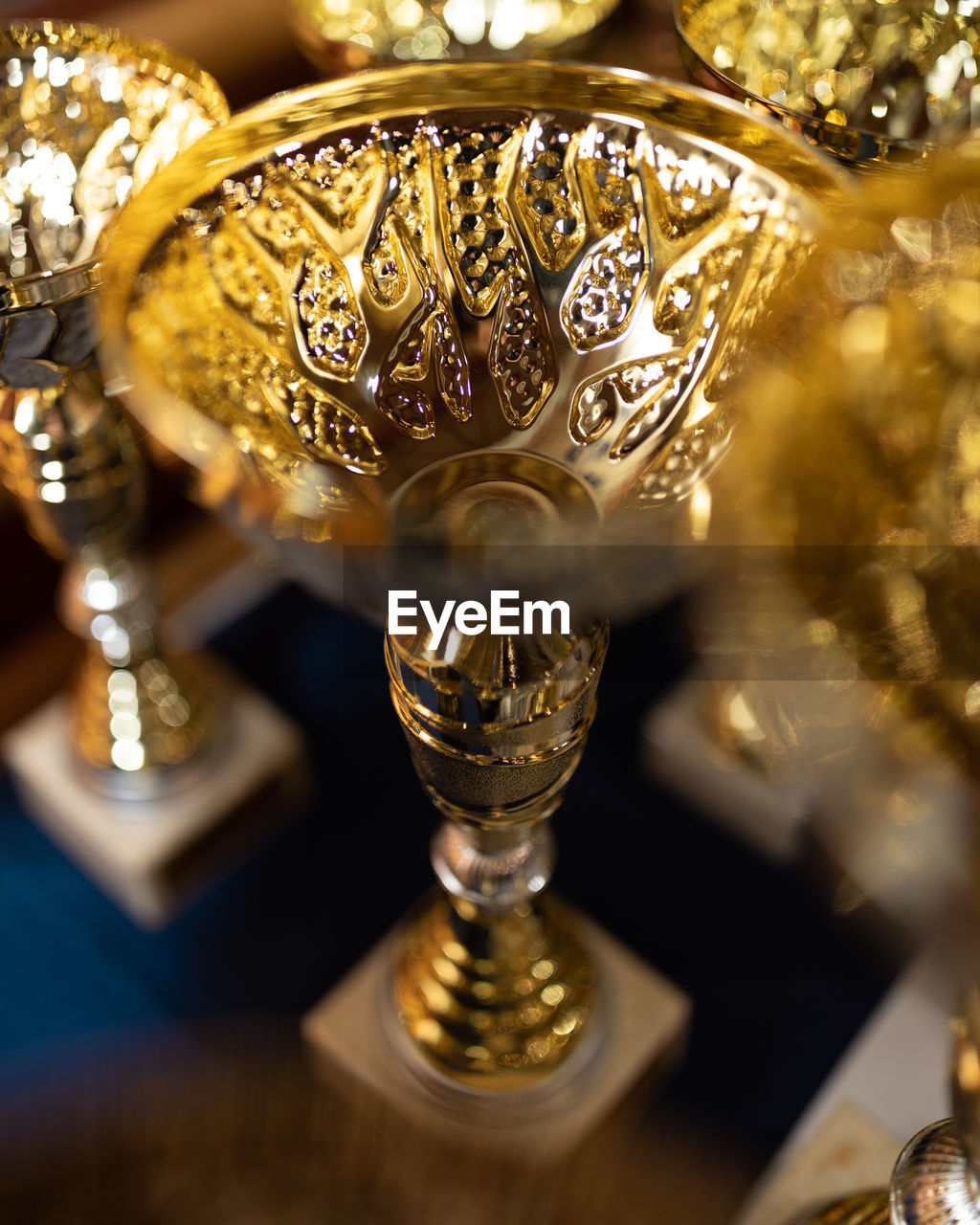 gold colored, no people, selective focus, close-up, metal, gold, still life, shiny, indoors, award, reflection, table, high angle view, success, ornate, silver colored, trophy, technology, design