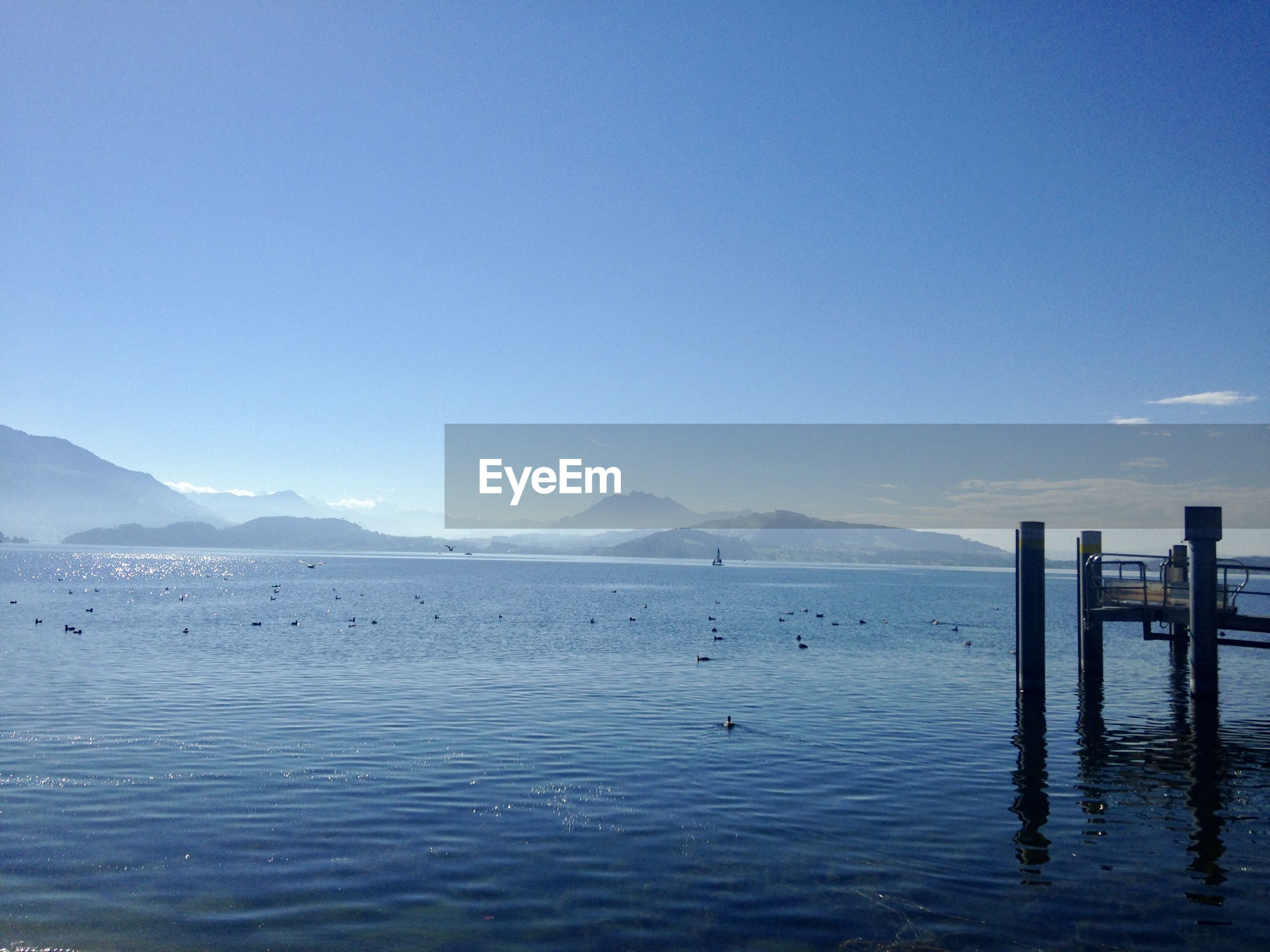 SCENIC VIEW OF SEA AND MOUNTAINS AGAINST CLEAR BLUE SKY