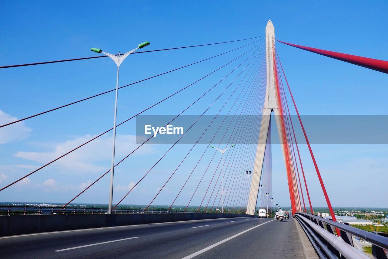 Empty road on bridge against blue sky