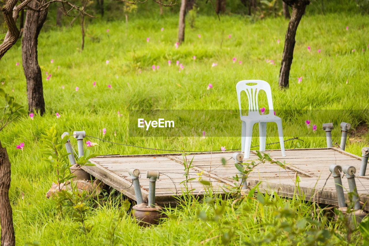 Chair on wooden platform against field