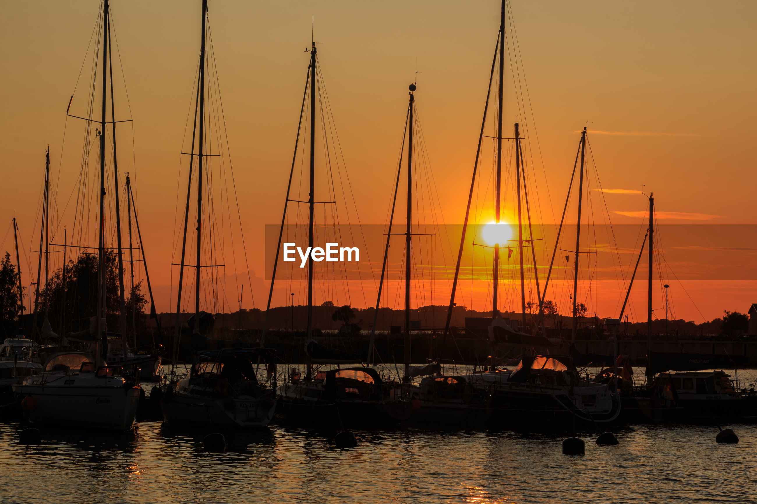SAILBOATS MOORED AT HARBOR AGAINST ORANGE SKY