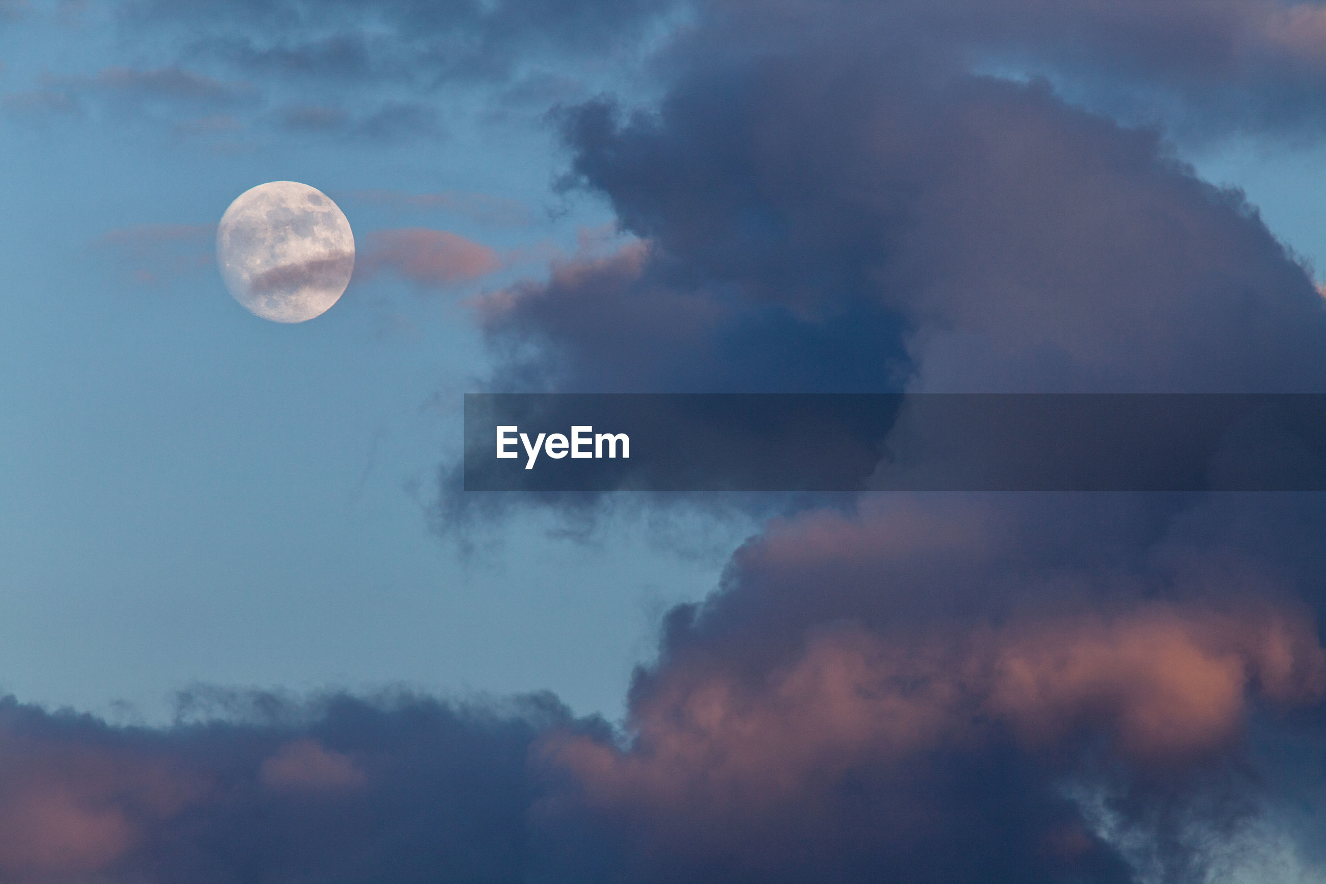 Low Angle View Of Cloudy Sky And Moon At Dusk