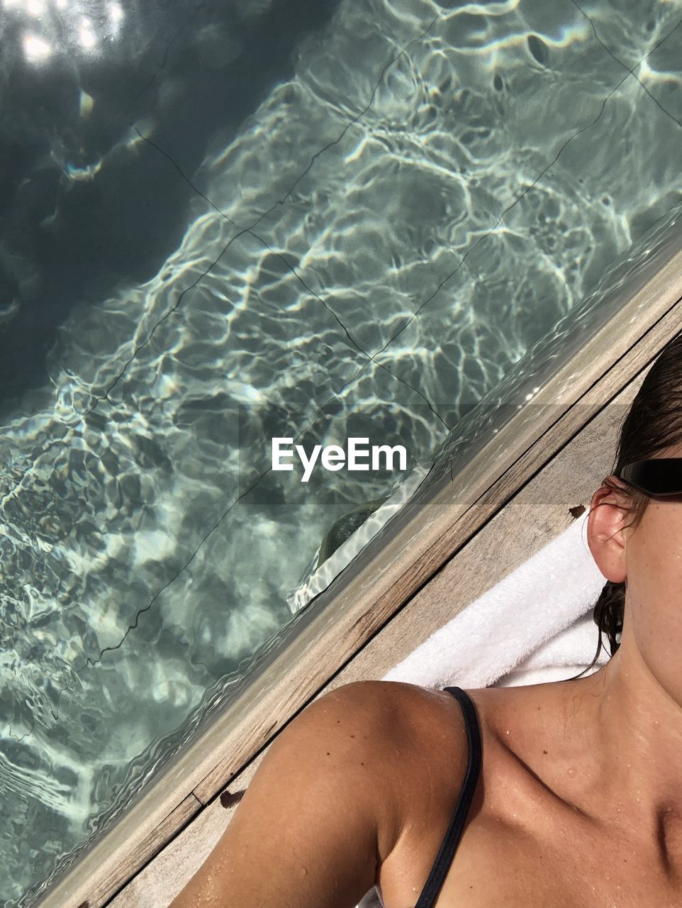 Cropped image of woman relaxing by swimming pool