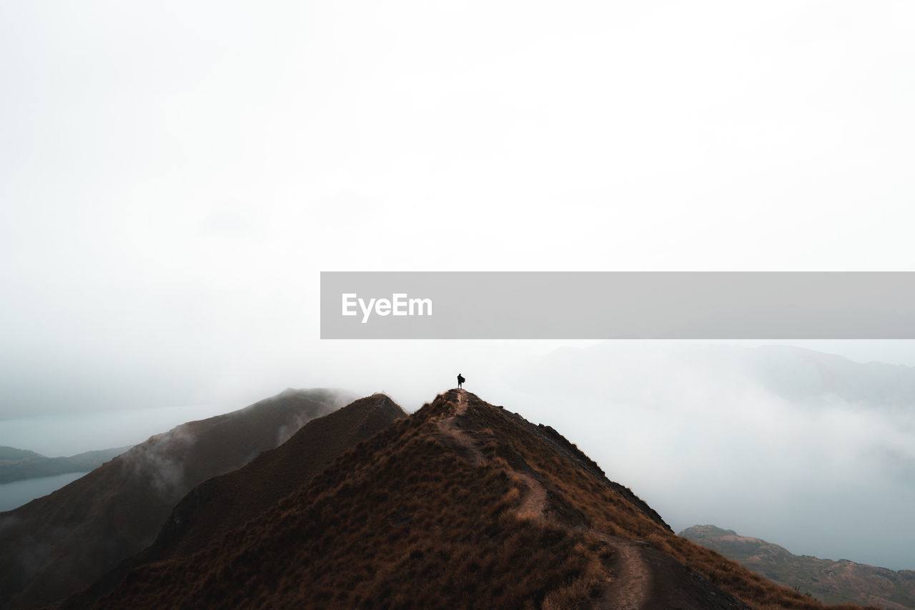 sky, mountain, scenics - nature, beauty in nature, tranquil scene, tranquility, copy space, fog, mountain range, nature, day, non-urban scene, environment, idyllic, remote, outdoors, landscape, land, no people, mountain peak, climate