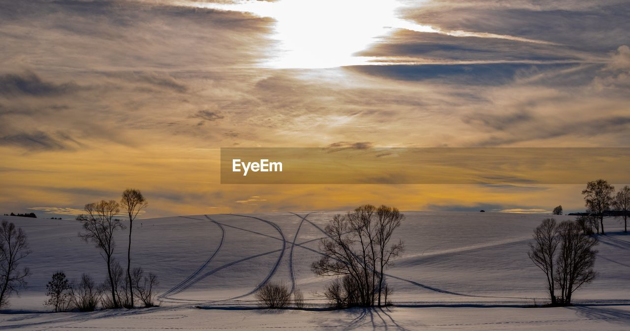 sky, sunset, beauty in nature, scenics - nature, winter, plant, tree, snow, cold temperature, water, tranquility, nature, cloud - sky, tranquil scene, no people, non-urban scene, lake, land, sun, outdoors