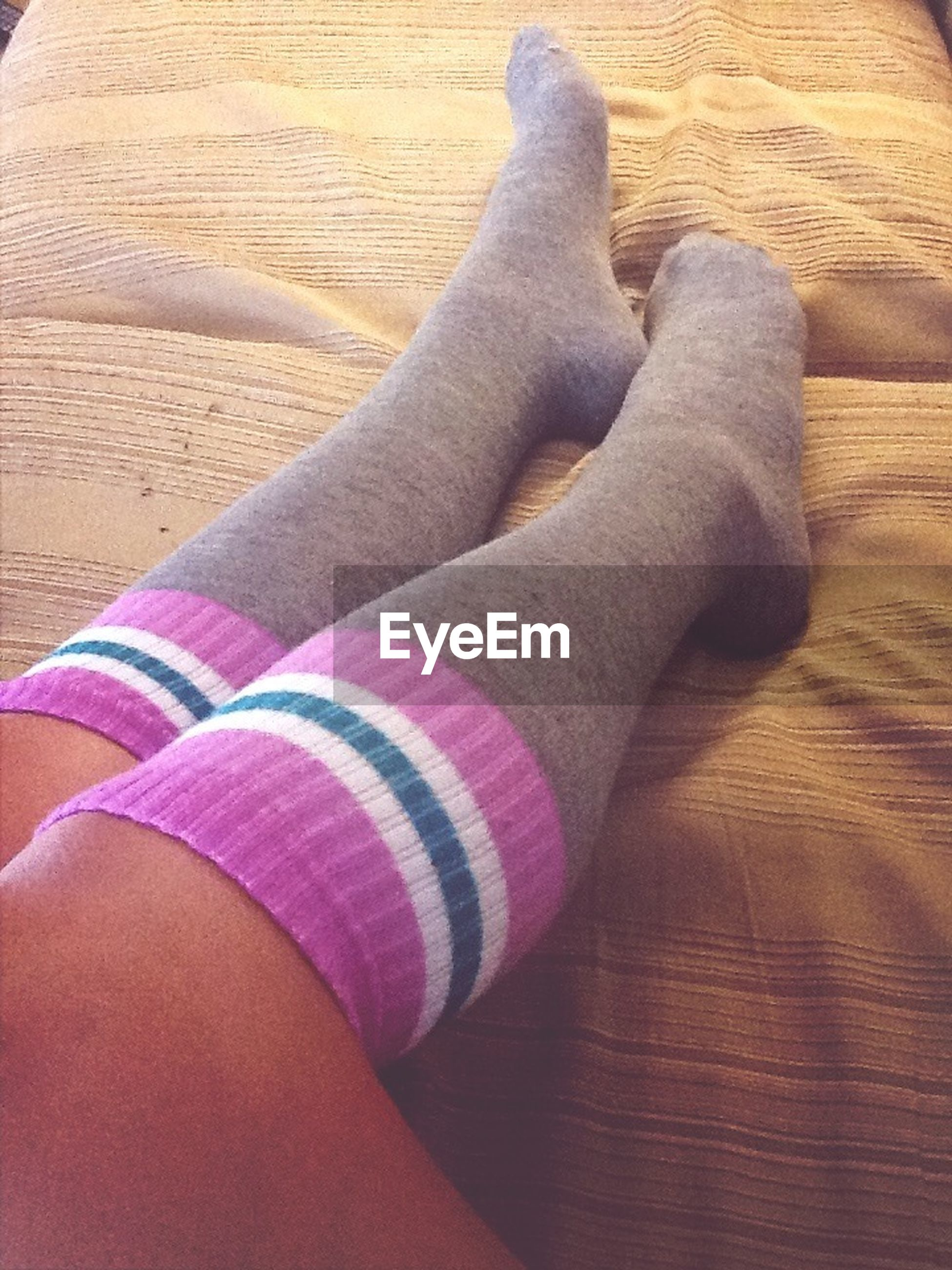 low section, person, high angle view, personal perspective, indoors, human foot, lifestyles, part of, close-up, relaxation, shoe, wood - material, barefoot, leisure activity, jeans, unrecognizable person