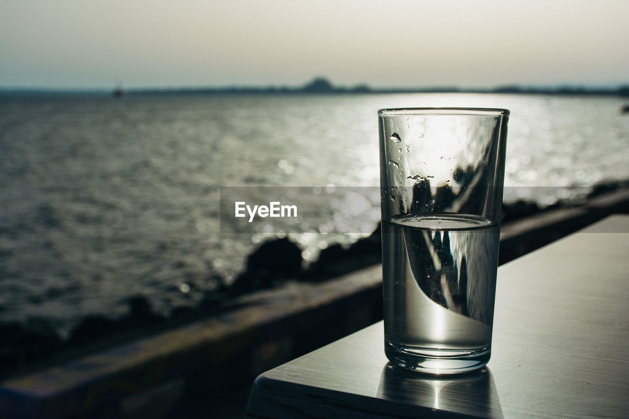 Glass Of Water On Table Against Sea During Sunset At Pomorie