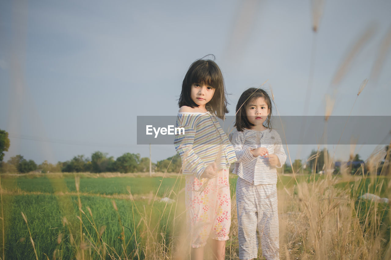Portrait of cute sisters standing on grassy field against sky