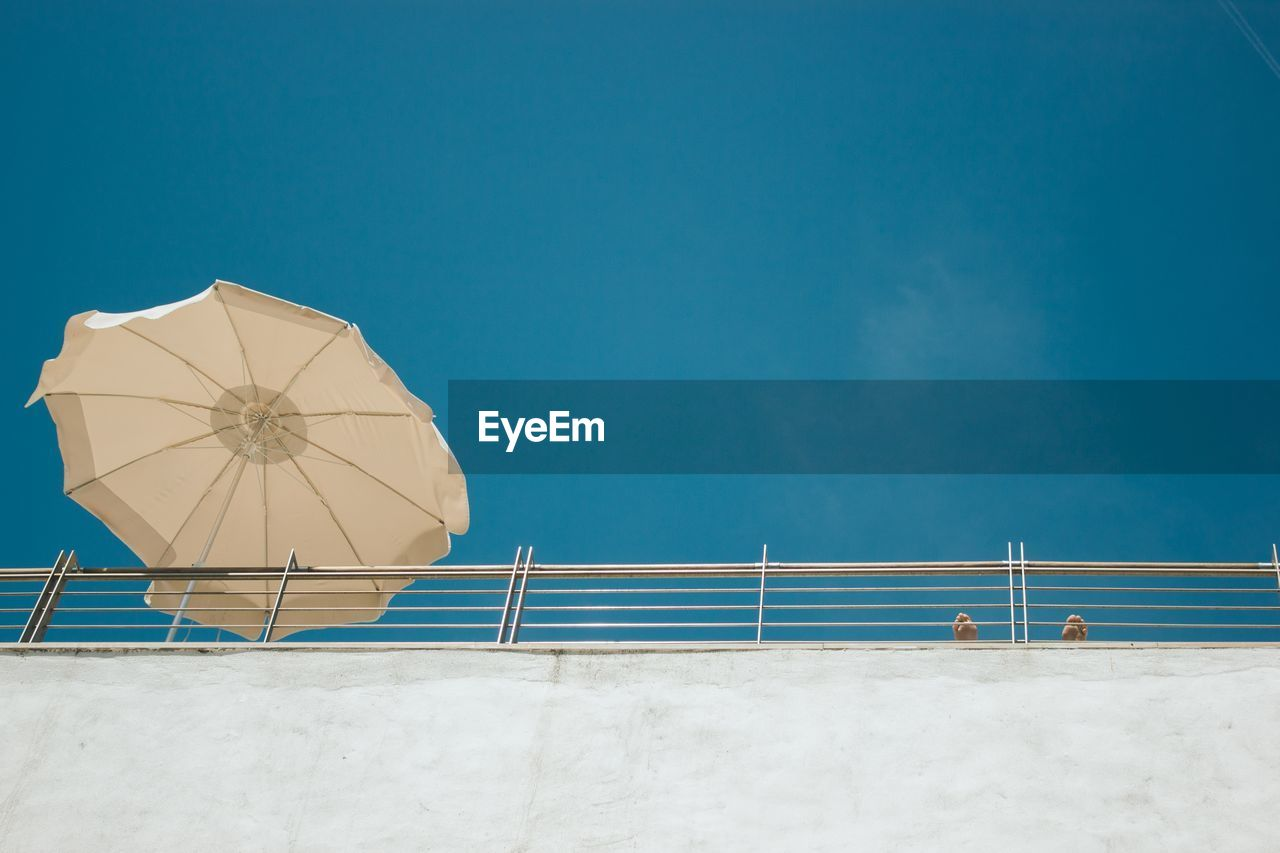 Low angle view of parasol by railing against clear blue sky