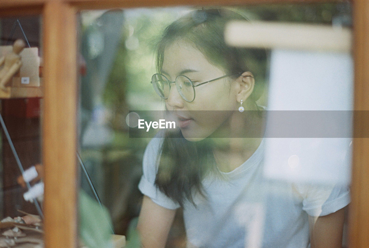 one person, real people, glasses, eyeglasses, looking, lifestyles, leisure activity, glass - material, young adult, casual clothing, young women, front view, transparent, women, window, headshot, reflection, contemplation, hairstyle, teenager, beautiful woman