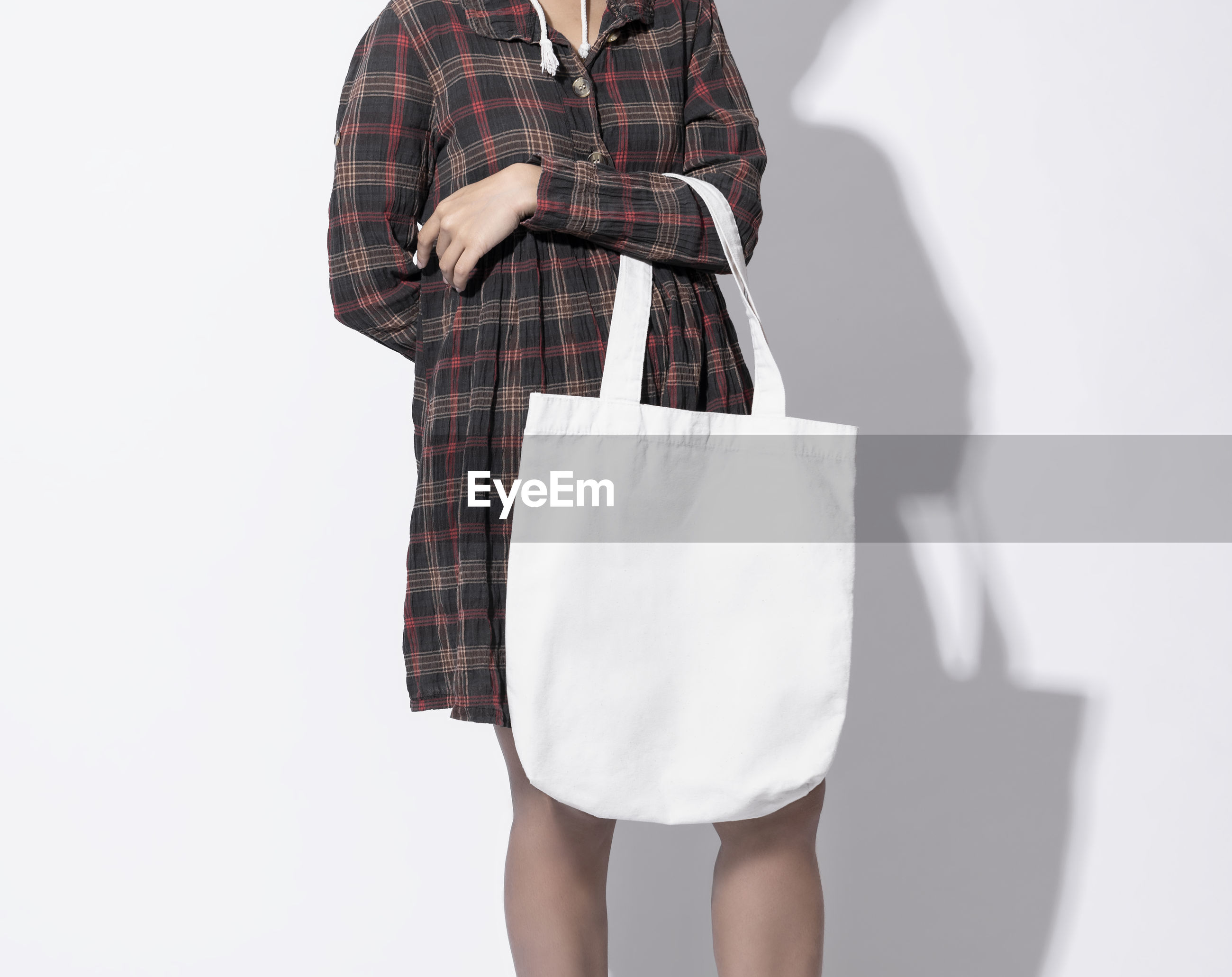 Midsection of woman holding bag against white background