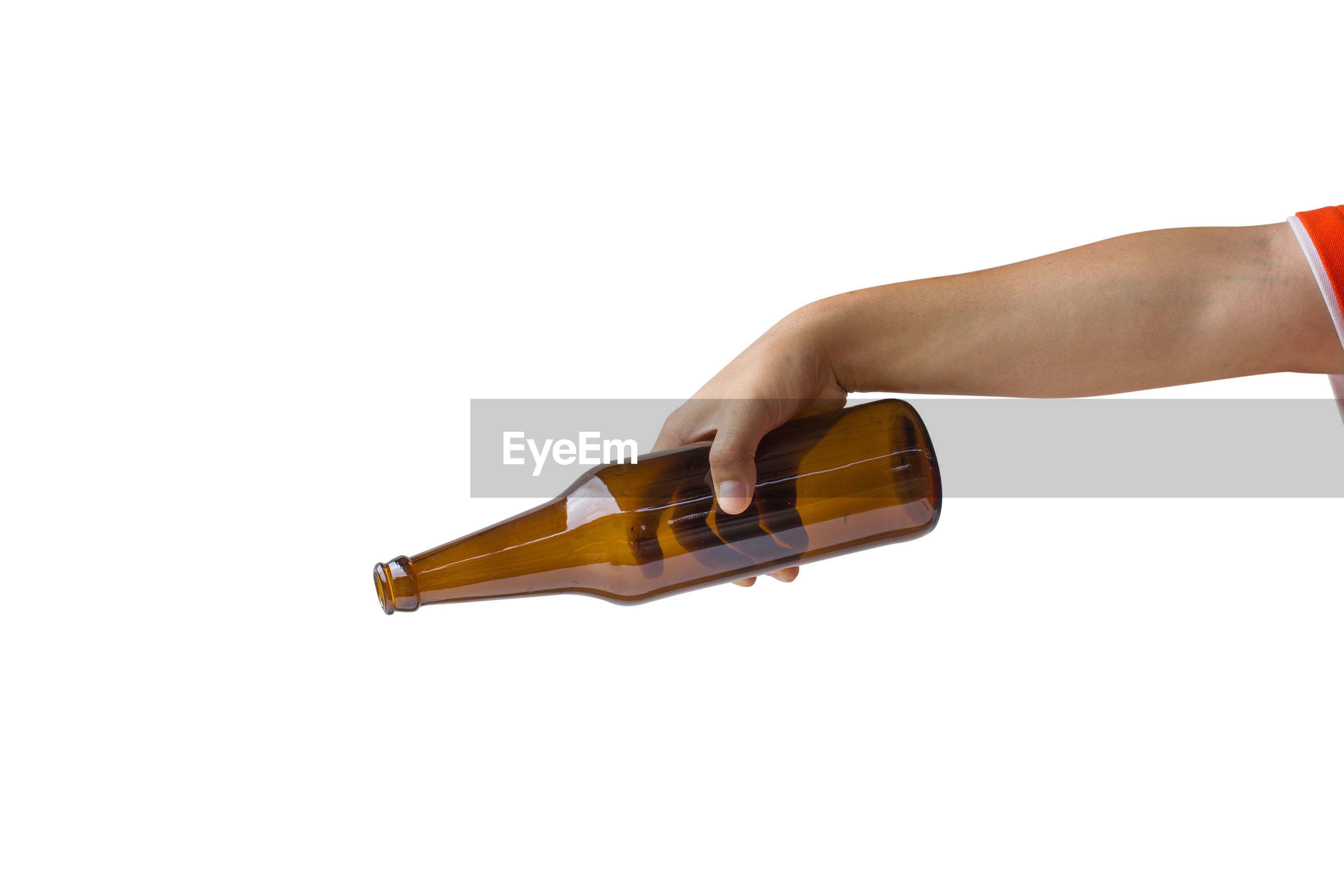 Cropped hand of person holding beer bottle against white background