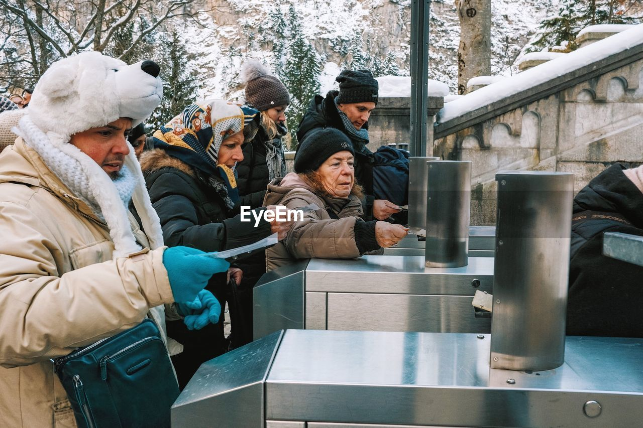 real people, cold temperature, warm clothing, winter, lifestyles, leisure activity, day, standing, men, snow, outdoors, technology, young adult, people