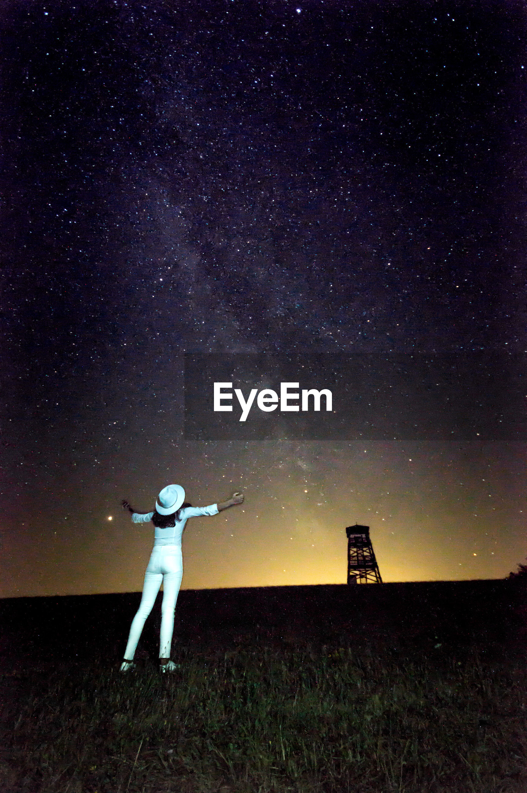 Full length rear view of girl standing against star field at night
