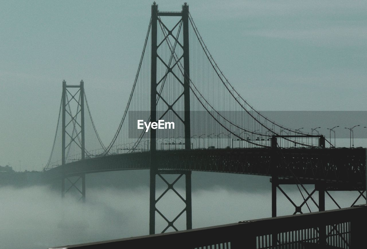 connection, bridge - man made structure, engineering, suspension bridge, architecture, transportation, built structure, bridge, cable, outdoors, river, day, sky, fog, water, no people, low angle view, travel destinations, tree, nature