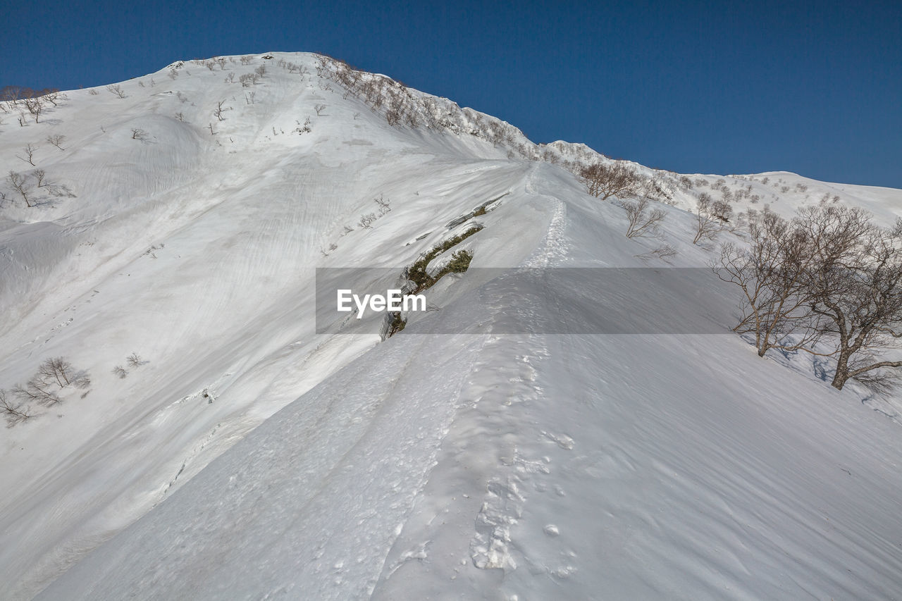 cold temperature, winter, snow, mountain, scenics - nature, beauty in nature, nature, sky, snowcapped mountain, environment, winter sport, land, landscape, day, non-urban scene, tranquil scene, desert, tranquility, leisure activity, mountain range, outdoors, climate, arid climate